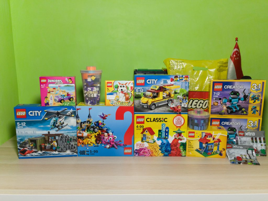 60150 Pizza Van, 10703 Creative Builder Box, 10404 Ocean's Bottom, 40235 Year of the Dog, 10677 Beach Trip, 60131 Crooks Island, 40154 Pencil Pot, two copies of 31062 Robo Explorer, 40311 Traffic Lights, 40312 Streetlamps, large and small Pick A Brick cups and a mystery set hidden in a LEGO Store shopping bag.